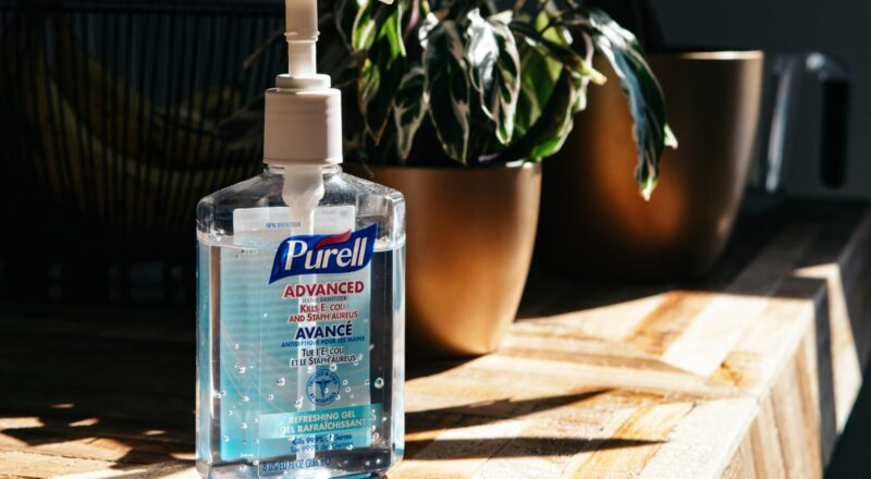 Purell sanitizer bottle on brown wooden table