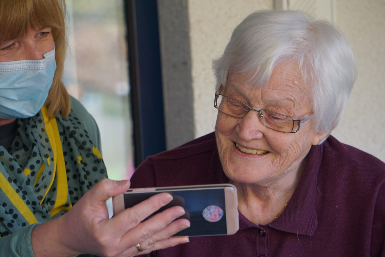 nurse with mask holding smartphone for elderly woman in nursing home